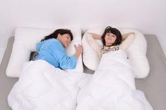 La muchacha con su momia está durmiendo en el malo Foto de archivo