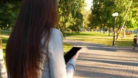 La muchacha con la tableta en un traje de negocios ligero va a trabajar la empresaria hermosa camina a lo largo del callejón en p metrajes