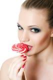 La muchacha con un caramelo de azúcar Foto de archivo