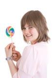 La muchacha con un caramelo de azúcar aislado en un blanco Fotos de archivo