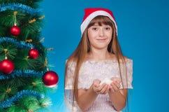 La muchacha con un casquillo en la cabeza cuesta cerca de un Año Nuevo elegante t Foto de archivo libre de regalías