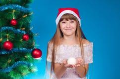 La muchacha con un casquillo rojo en la cabeza cuesta cerca de nuevo YE elegante Fotografía de archivo libre de regalías