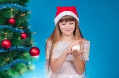 La muchacha con un casquillo rojo en la cabeza cuesta cerca de nuevo YE elegante Foto de archivo libre de regalías