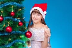 La muchacha con un casquillo rojo en la cabeza cuesta cerca de una nueva Y hermosa Fotos de archivo libres de regalías