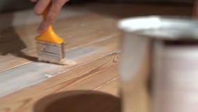 La muchacha con un cepillo pinta a los tableros de madera en el aceite blanco metrajes