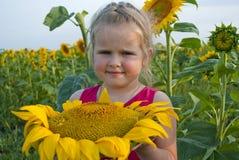 La muchacha con un girasol enorme Foto de archivo libre de regalías