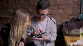 La muchacha con un individuo en un café encontró en la tableta algo divertido almacen de metraje de vídeo