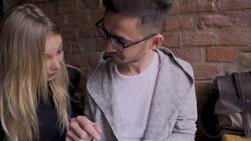 La muchacha con un individuo en un café encontró en la tableta algo divertido almacen de video