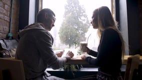 La muchacha con un individuo en un café pasa un buen rato mientras que él el ` s que llueve afuera almacen de video
