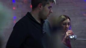 La muchacha con un individuo jura en un partido La muchacha está bebiendo píldoras El individuo prueba su posición almacen de metraje de vídeo