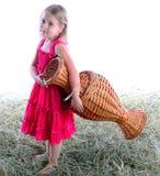 La muchacha con un jarro wattled descalzo en el heno Imagen de archivo
