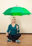 La muchacha con un paraguas verde se sienta en el piso Imagenes de archivo