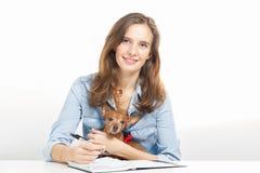 La muchacha con un pequeño perrito escribe notas Fotografía de archivo libre de regalías
