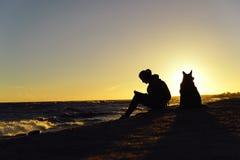 La muchacha con un perro en la costa Foto de archivo libre de regalías