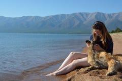 La muchacha con un perro está en la orilla del lago Baikal Fotografía de archivo