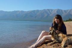 La muchacha con un perro está en la orilla del lago Baikal Fotos de archivo libres de regalías