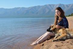 La muchacha con un perro está en la orilla del lago Baikal imagen de archivo