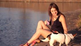 La muchacha con un perro se sienta cerca de un lago en la puesta del sol almacen de video