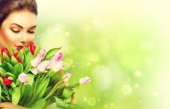 La muchacha con un ramo de tulipán colorido florece Foto de archivo