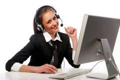 La muchacha con un receptor de cabeza trabaja en el ordenador Fotografía de archivo libre de regalías