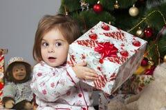 La muchacha con un regalo bajo el árbol de navidad Imágenes de archivo libres de regalías