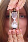 La muchacha con un reloj de la arena Imagenes de archivo