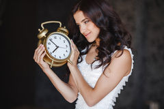 La muchacha con un reloj grande en un fondo oscuro Imagen de archivo