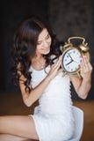 La muchacha con un reloj grande en un fondo oscuro Fotografía de archivo