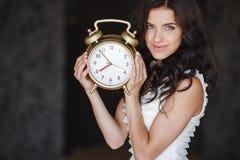 La muchacha con un reloj grande en un fondo oscuro Imagenes de archivo
