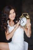 La muchacha con un reloj grande en un fondo oscuro Imágenes de archivo libres de regalías