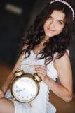 La muchacha con un reloj grande en un fondo oscuro Foto de archivo libre de regalías