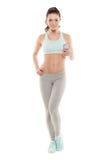 La muchacha con un smartphone en un fondo blanco, disfruta de deportes entrenando, entrenamiento de la aptitud del gimnasio Fotos de archivo