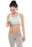 La muchacha con un smartphone en un fondo blanco, disfruta de deportes entrenando, entrenamiento de la aptitud del gimnasio Fotografía de archivo libre de regalías