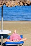 La muchacha con un sombrero rojo está en costa de mar Foto de archivo