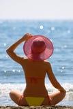 La muchacha con un sombrero rojo está en costa de mar Fotografía de archivo libre de regalías