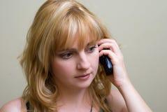 La muchacha con un teléfono móvil en una mano Imagen de archivo libre de regalías