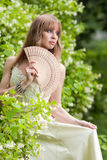 La muchacha con un ventilador en una alineada blanca Foto de archivo libre de regalías