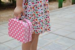 La muchacha con un vestido y una maleta rosada juegan imágenes de archivo libres de regalías