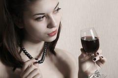 La muchacha con un vidrio de vino. Fotografía de archivo libre de regalías