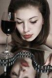 La muchacha con un vidrio de vino. Imagen de archivo