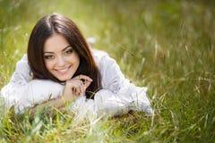 La muchacha con una almohada en la hierba fresca de la primavera Fotografía de archivo libre de regalías