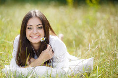 La muchacha con una almohada en la hierba fresca de la primavera Fotografía de archivo