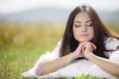 La muchacha con una almohada en la hierba fresca de la primavera Fotos de archivo