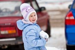 La muchacha con una bola de nieve en manos Fotos de archivo libres de regalías