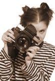 La muchacha con una cámara vieja en una mano Fotos de archivo