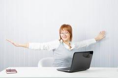 La muchacha con una computadora portátil estira en el lugar de trabajo Foto de archivo