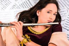 La muchacha con una flauta y las notas Fotografía de archivo