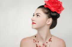 La muchacha con una flor roja Fotografía de archivo