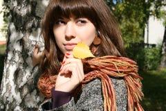 La muchacha con una hoja del otoño. Foto de archivo libre de regalías