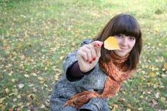 La muchacha con una hoja del otoño. Imágenes de archivo libres de regalías